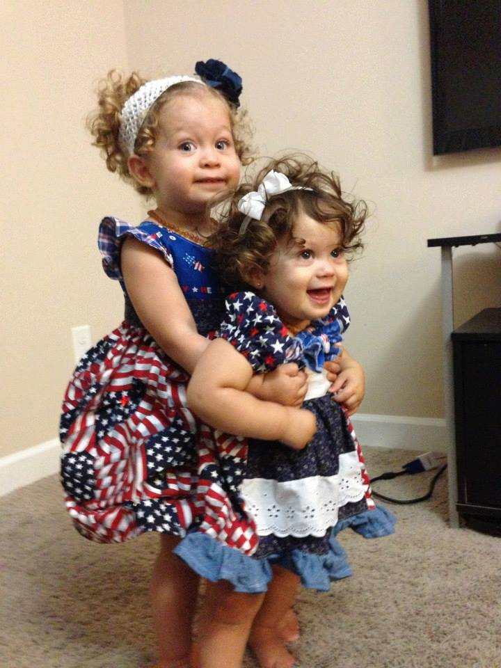 Sisters pose together on the Fourth of July. They are wearing homemade patriotic dresses.