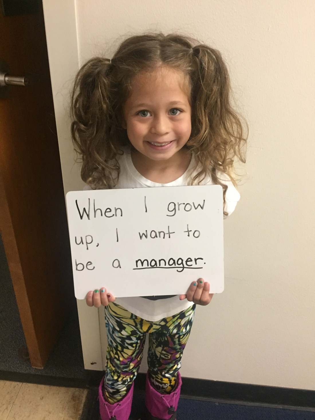 "A little girl with pigtails holds a sign that reads ""When I grow up, I want to be a manager."""