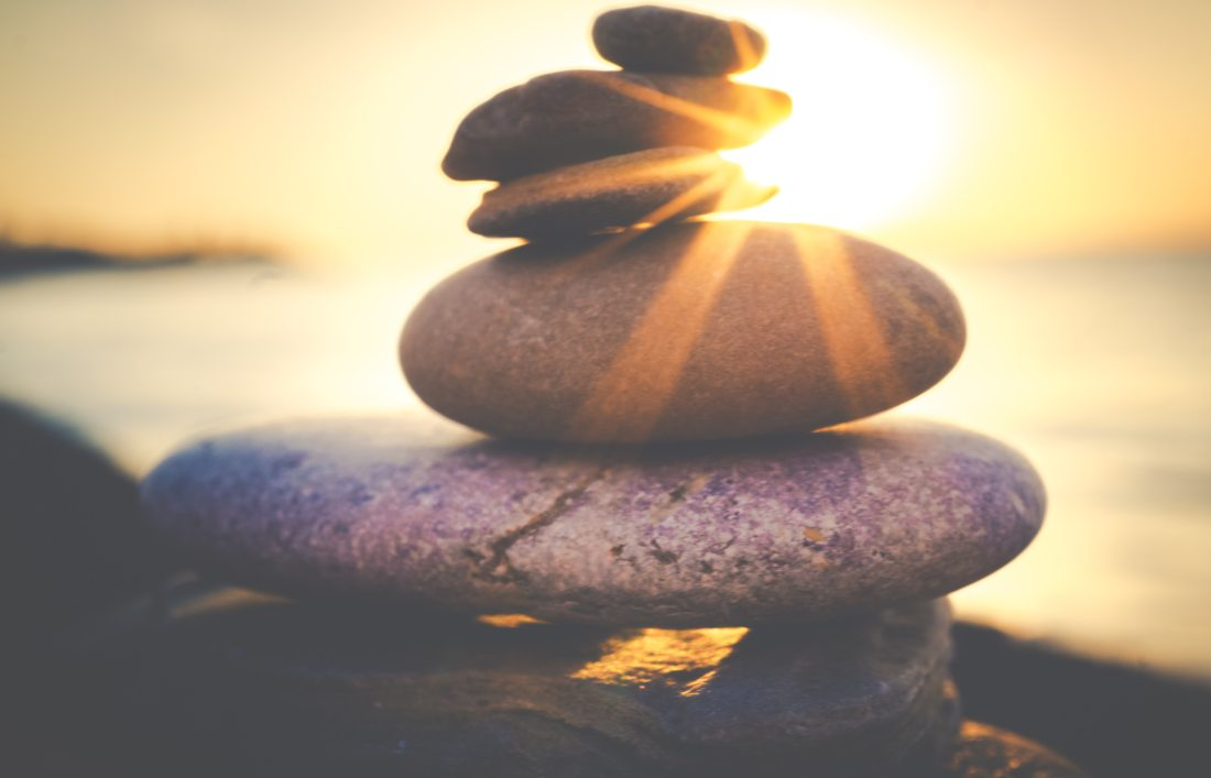 a rising sun shines through a pile of stones in front of a body of water.