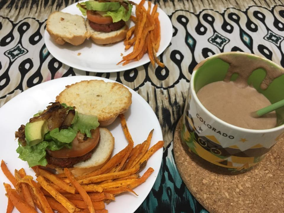 Food photography of two Beyond Burgers with cartelized onions and sweet potato fries with a Colorado mug full of chocolate shake.