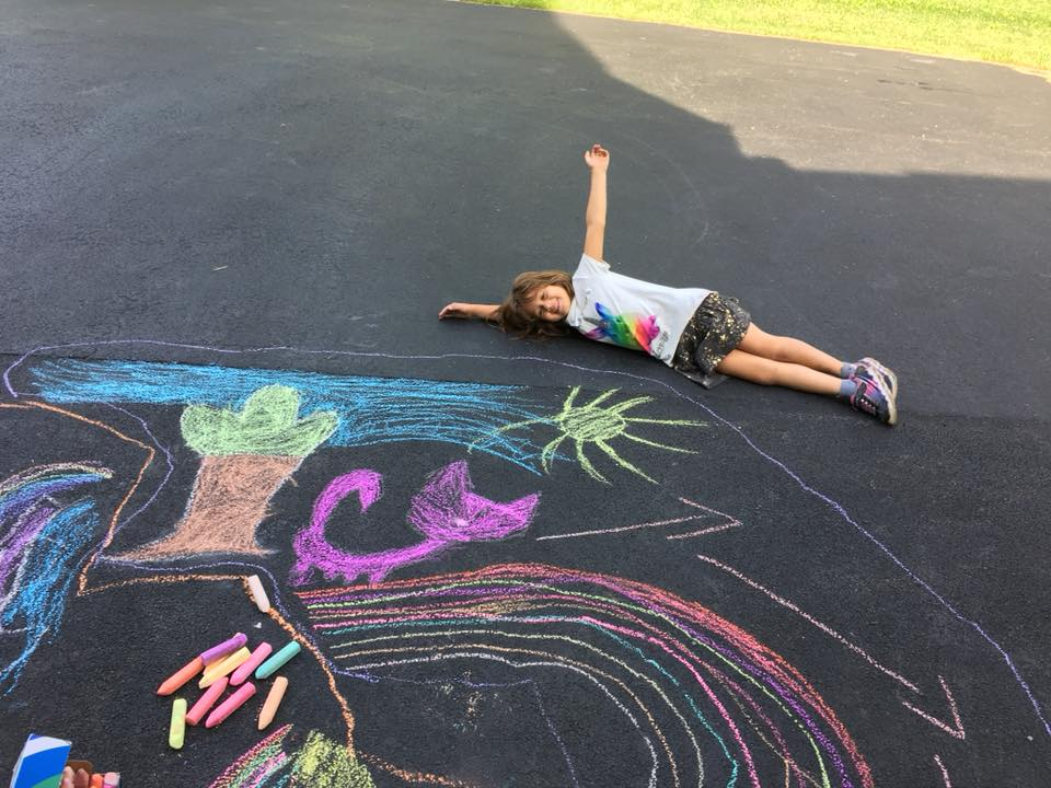 A little girl lays on a driveway next to her chalk art of a tree, sun, cat, and rainbow. Rainbow chalk is spread on the driveway.