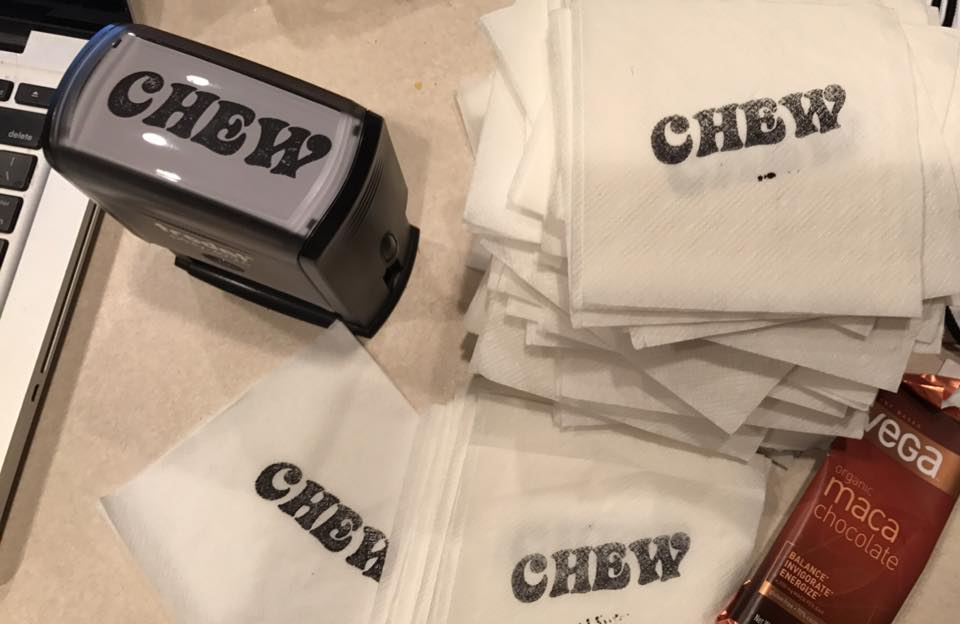 beverage napkins stamped with CHEW are next to a CHEW stamp.