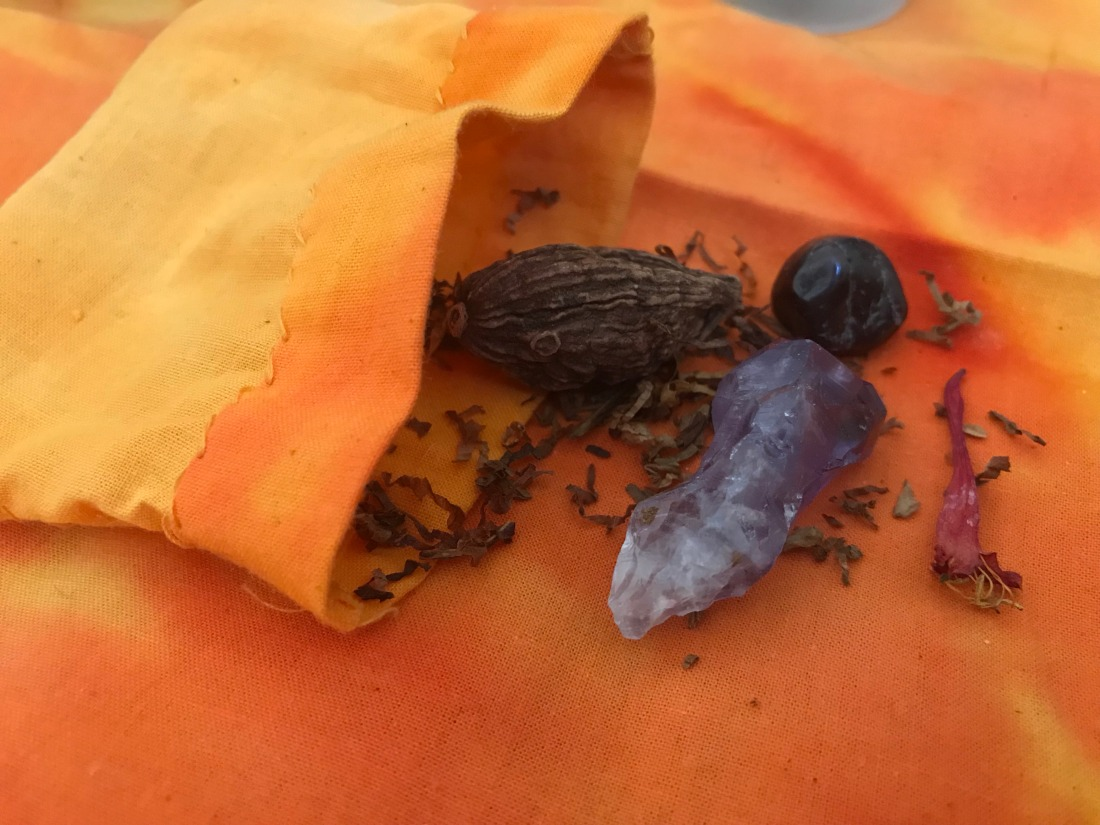The contents of an orange bag are spilled out onto an orange altar cloth. there is tobacco, nutmeg, amethyst, garnet, and honeysuckle.
