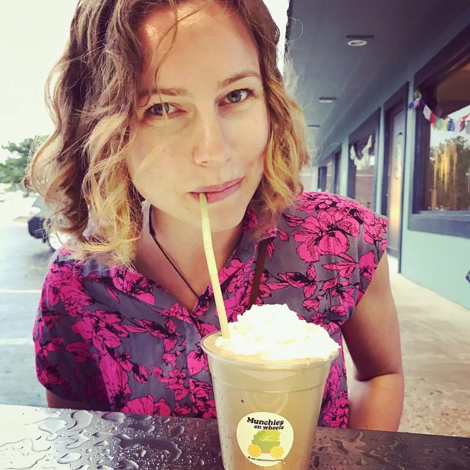 A customer sips a vegan peanut butter cup shake through a straw in front of Satya yoga studio.
