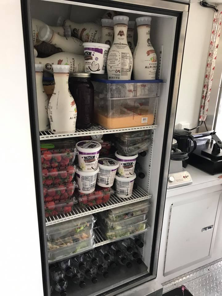 A fully stocked refrigerator in a food trailer holds Califia farms coconut almond milk, waffle batter, coconut yogurts, strawberries, prepped salads, and Essential waters.