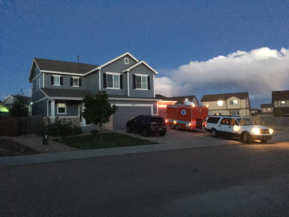 A white SUV backs a red food trailer into a driveway in front of a big blue house at dusk.