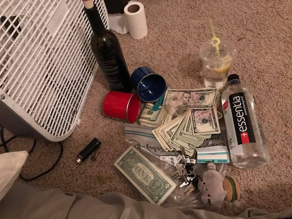 Stacks of crisp dollar bills, trailer keys, an essentia water bottle, cup of water with a yellow curly straw, bottle of wine, two tin camping mugs, a lighter, a fan, and a roll of toilet paper on a carpeting floor next to a mattress.