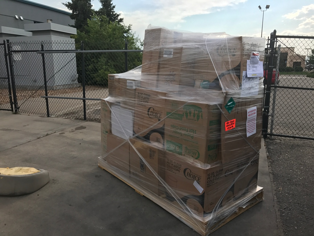 A pallet of boxes of biodegradable and recyclable disposables is wrapped up in cellophane in front of a warehouse.