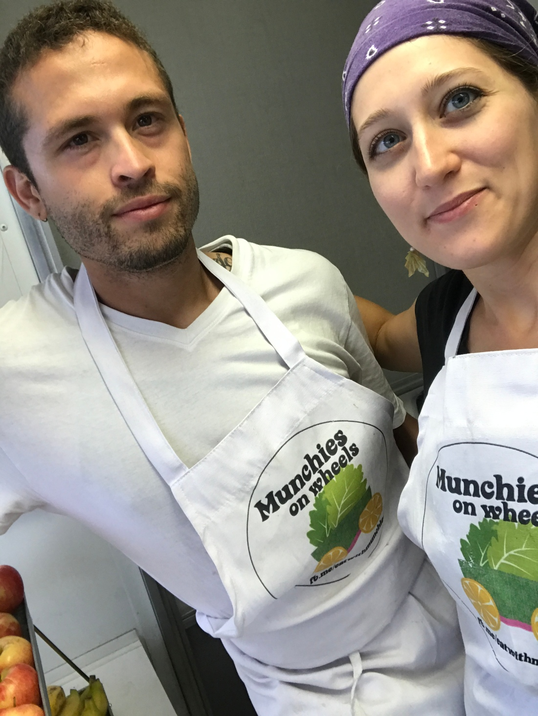 José Mojica and Stacy Mojica stand together wearing Munchies on Wheels aprons.
