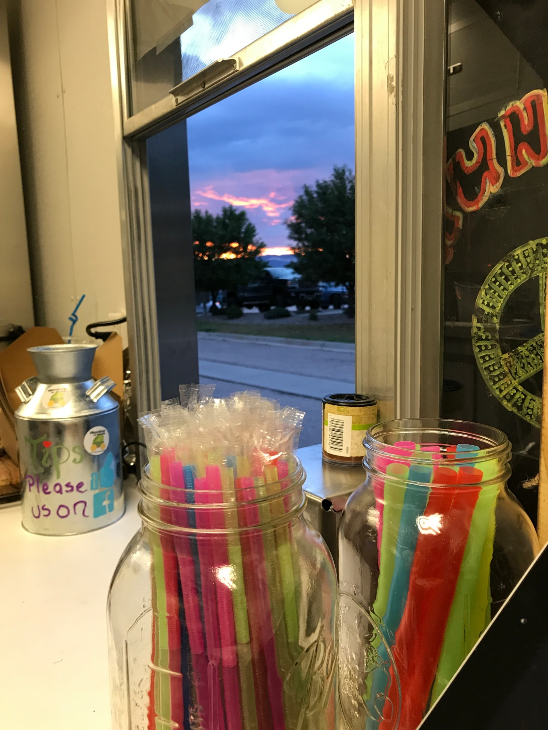 A view through the window of the food trailer shows the Colorado sky at sunset.