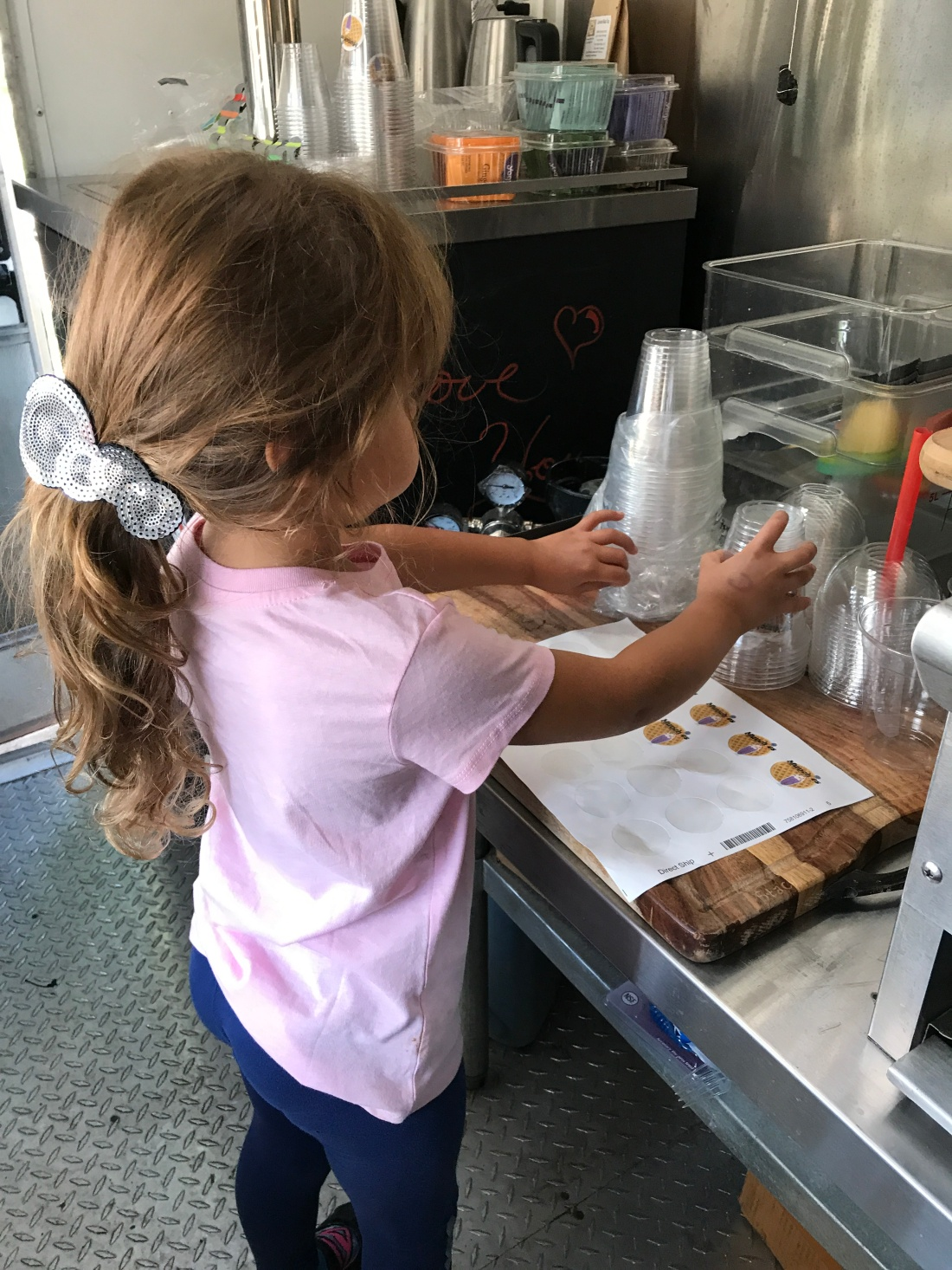 A girl puts stickers on cups in a food trailer.
