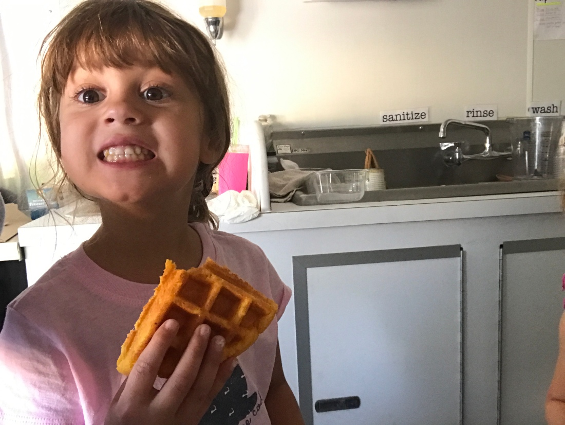 "A girl holding a waffle smiles. Behind her is a three part sink that says ""wash,"" rinse,"" and ""sanitize."""