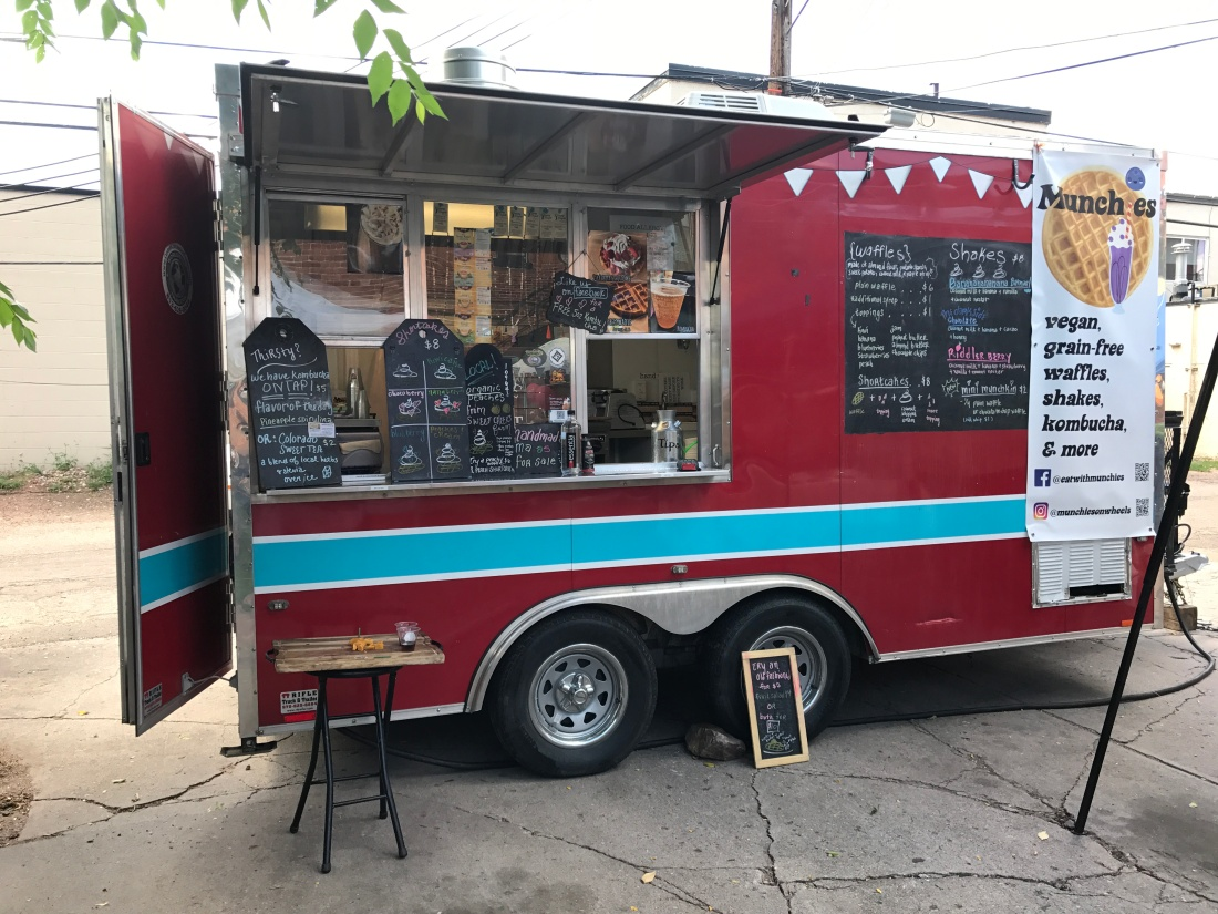 """A red food truck with a banner that reads """"Munchies. vegan, grain-free waffles, shakes, kombucha, & more."""""""