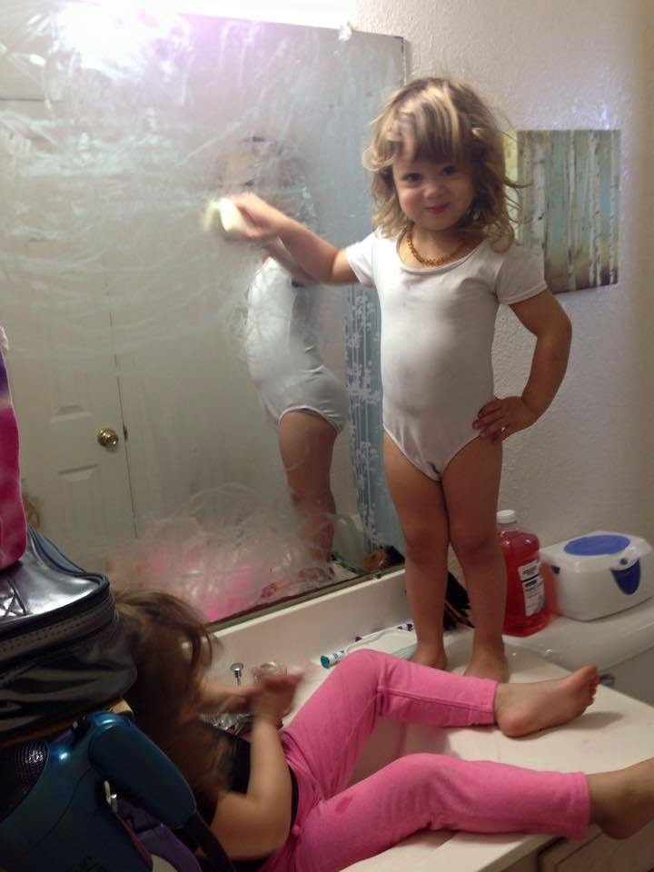Two toddler sisters play in the bathroom sink. One is standing on the sink and drawing on the mirror with soap.