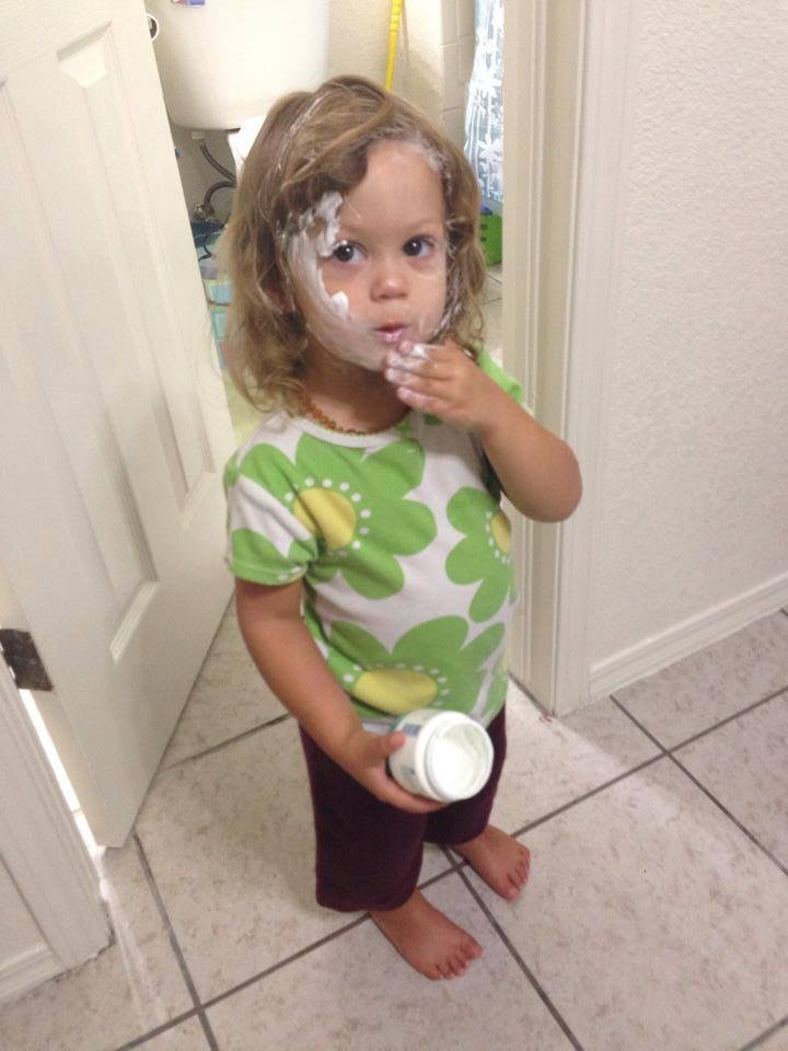 A toddler smears medicated diaper rash cream on her face.