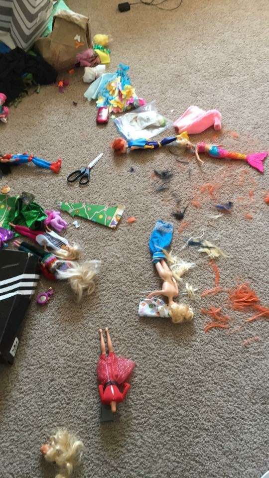 A massacre of barbies on the floor. Many have had their hair cut. Scissors and barbie hair are on the floor. One barbie's head has popped off.