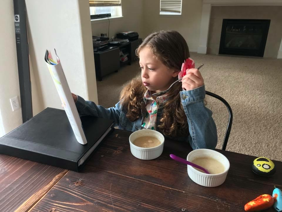 A girl eats cream of wheat and reads a magazine before school.