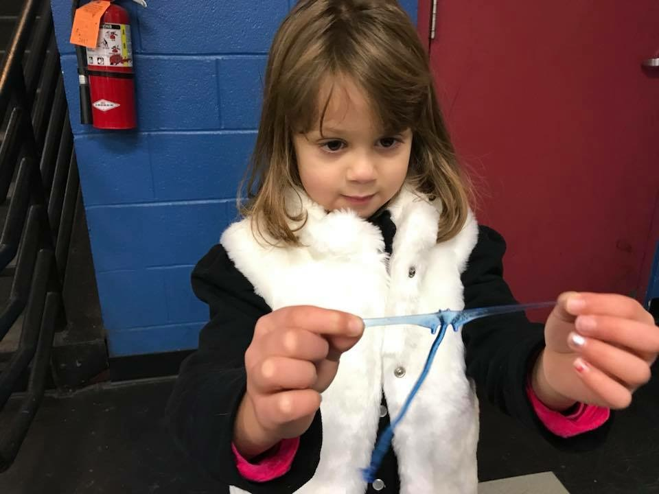 A five year old stretches out a blue butterfly cling toy so that it looks like a bat.