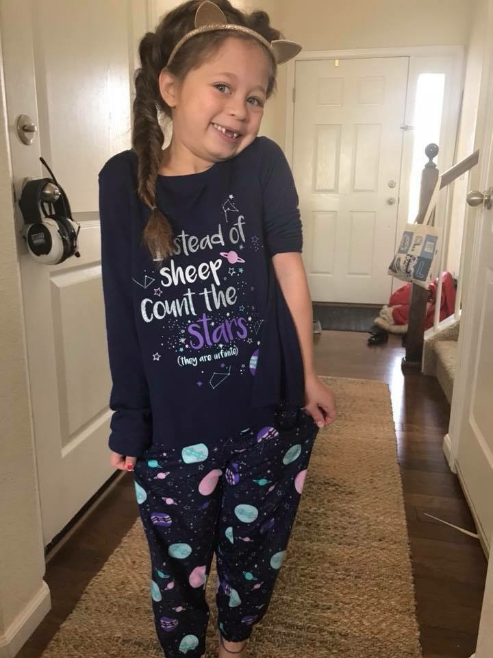 "A girl with gold cat ears and a fishtail braid poses in her new pajamas that say ""Instead of sheep count the stars (they are infinite)."