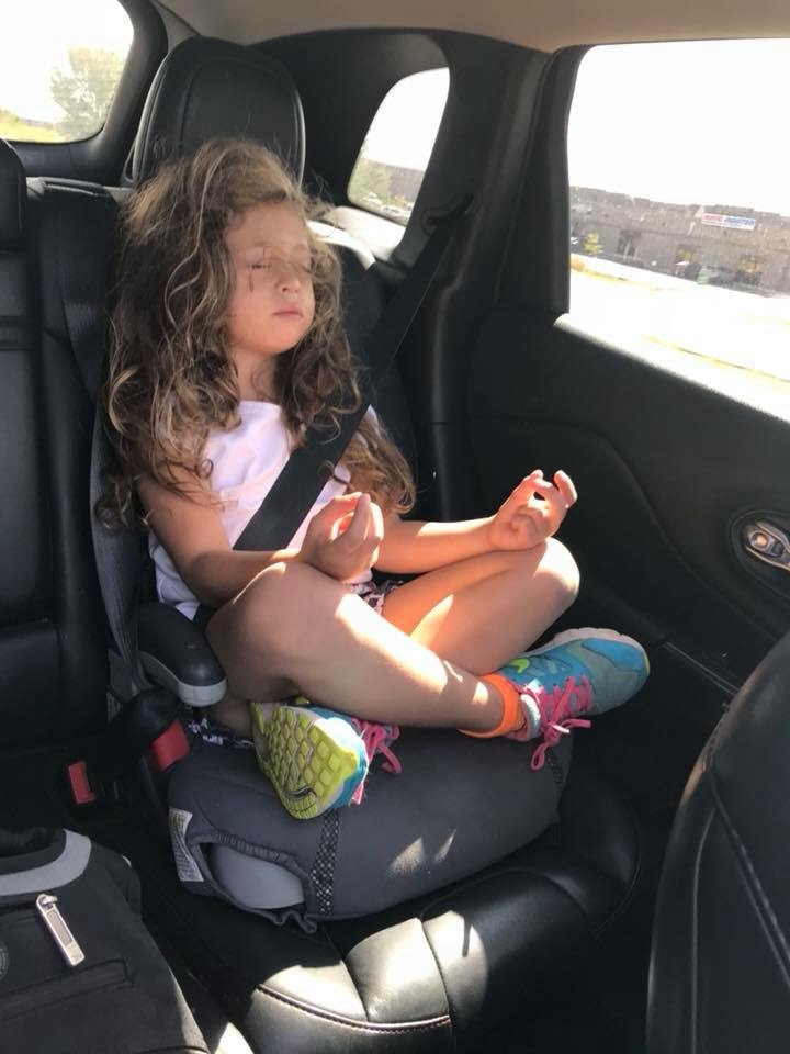A little girl mediates in her carseat in the car.