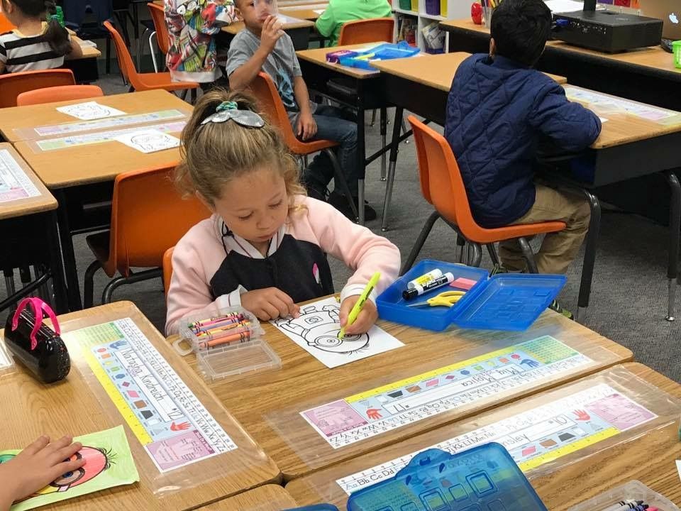 A girl colors a picture on her first day of school in first grade.
