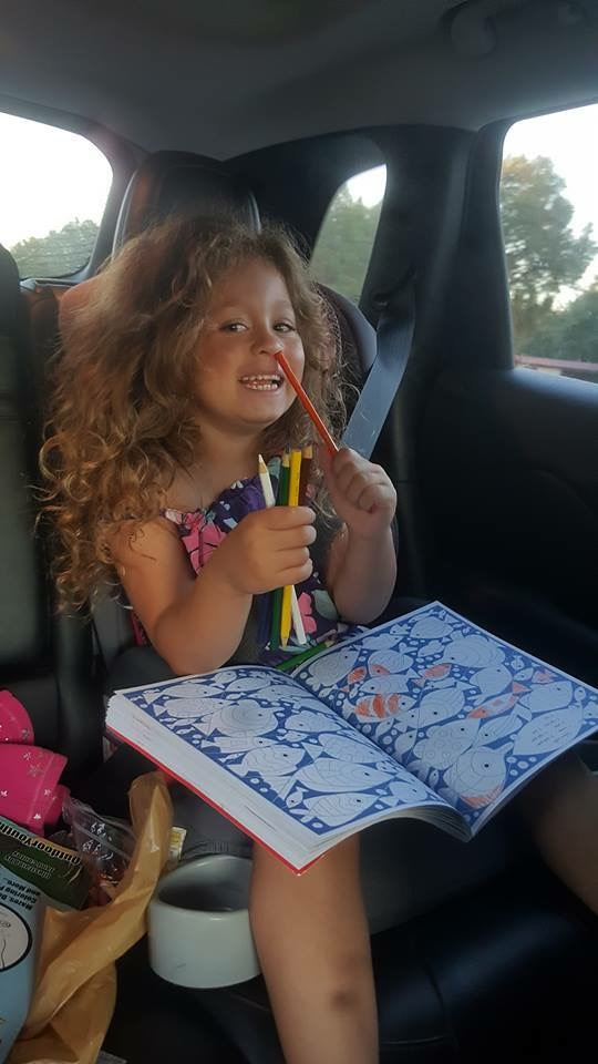 A girl in a booster seat in a car with a coloring book on her lap sticks a pencil in her nose.