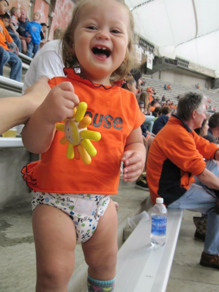 Baby wearing cloth diaper and orange Syracuse t-shirt holds a wooden sun toy and smiles at a sport's game.