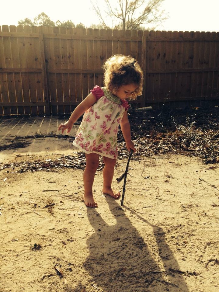 A barefoot little girl holds a stick to the dirt in a backyard in Georgia.