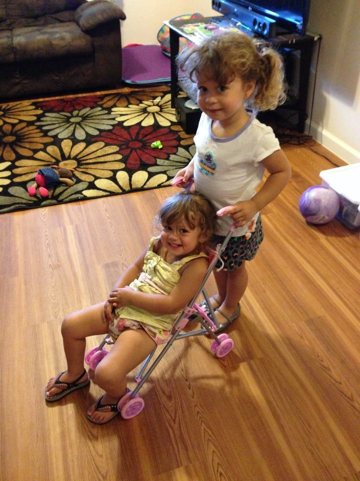 A big sister pushes a little sister in a doll stroller.
