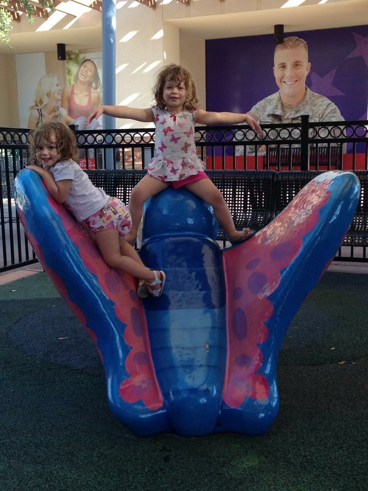 Two little girls play on a play structure in the shape of a butterfly.