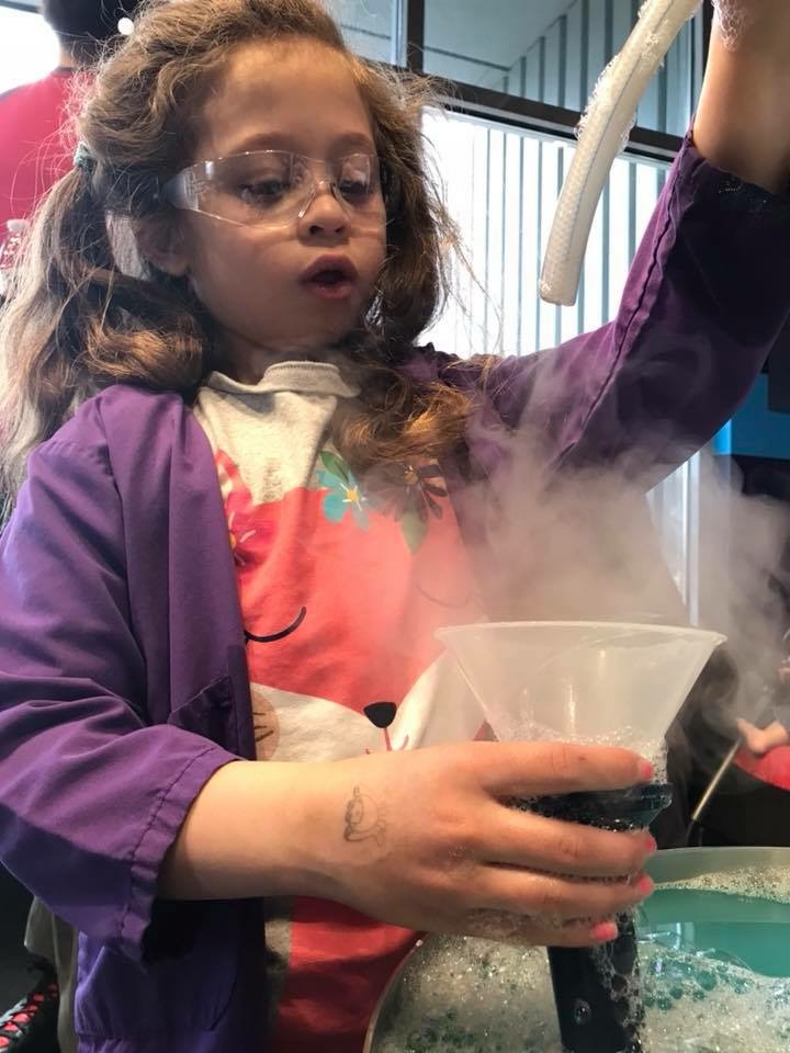 A girl wearing a lab coat and protective glasses is fascinated by the science of bubbles.
