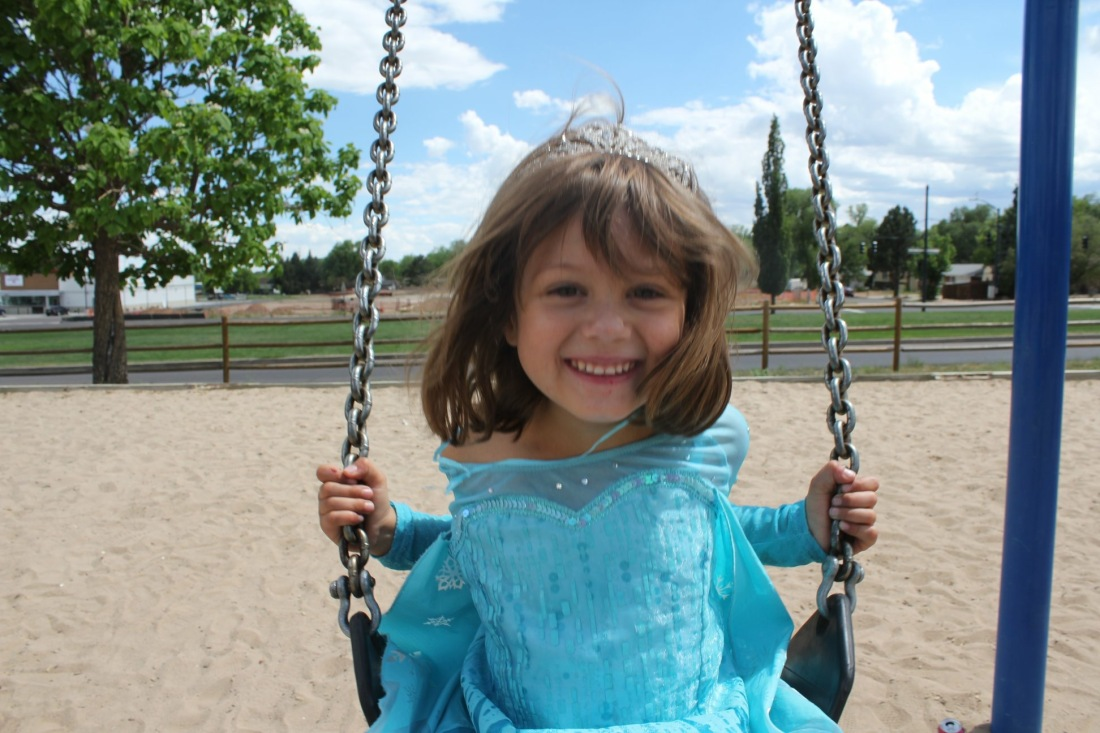 A little girl smiles on a swing on her birthday.