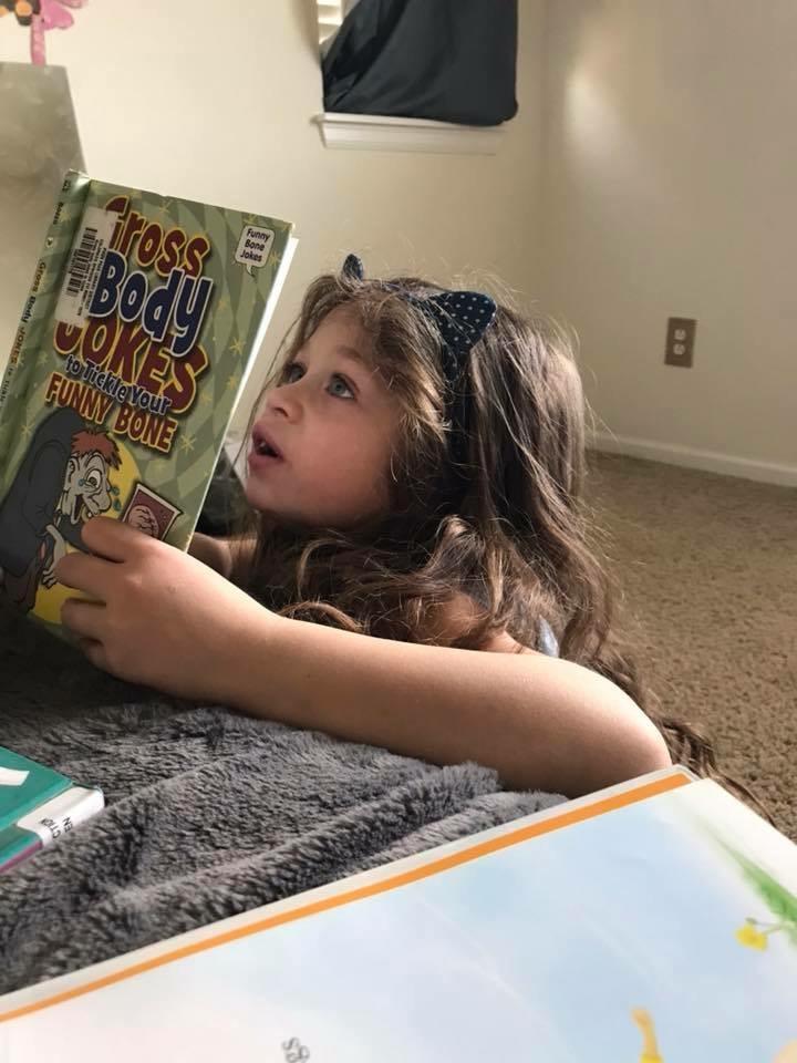 """A girl reads a book titled """"Gross Body Jokes"""""""