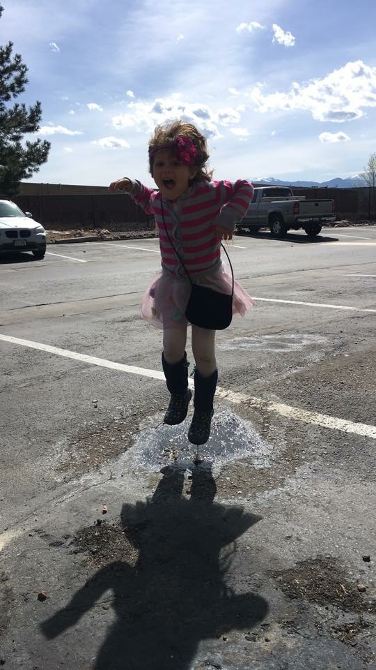 A little girl jumps in a puddle in a parking lot with a beautiful blue sky behind her.