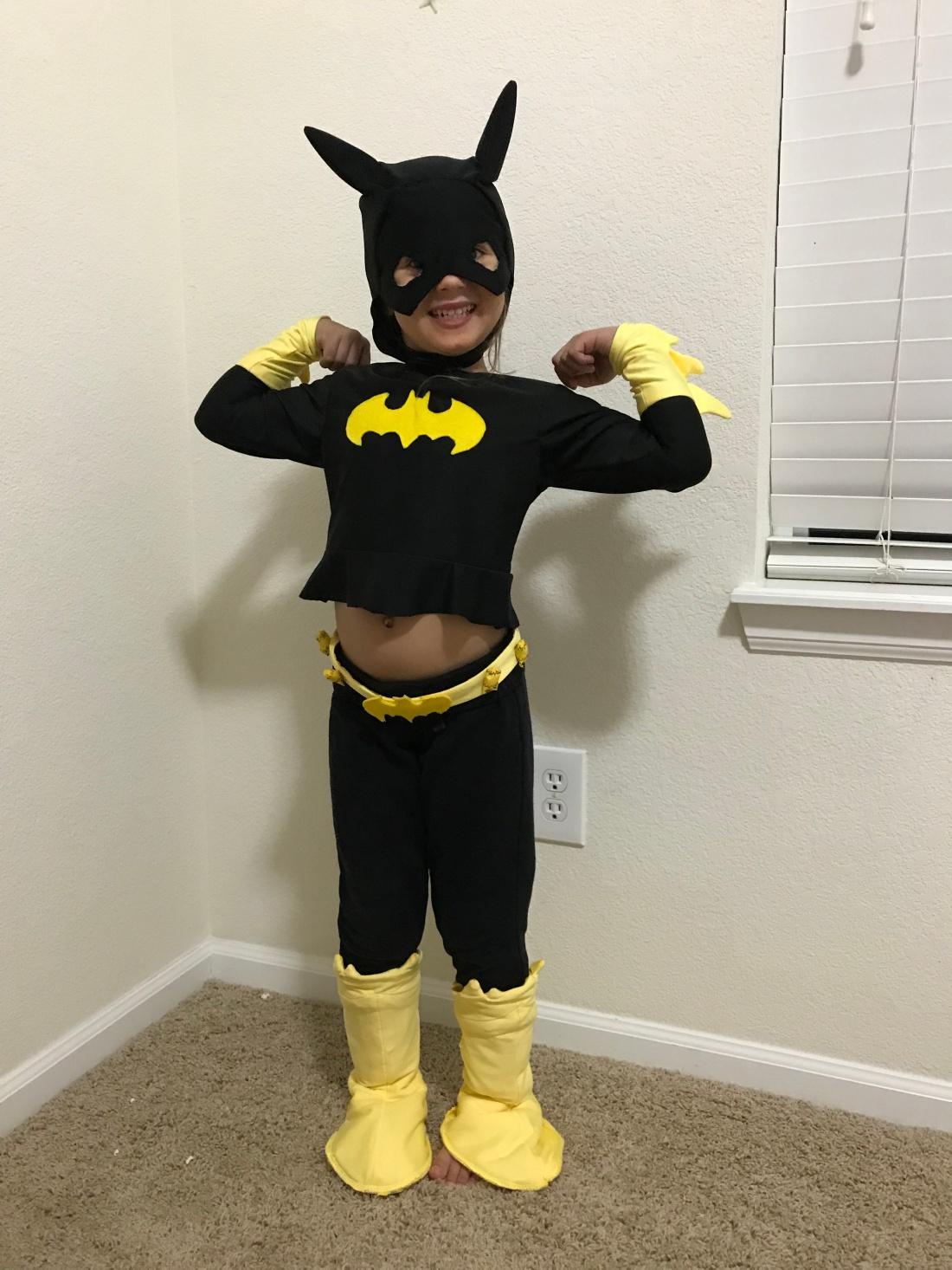 A little girl wears a homemade Batman costume.