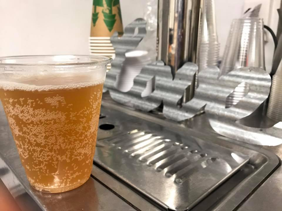 """kombucha full of bubbles in a plastic cup is in front of a kegerator and the word """"Love."""""""
