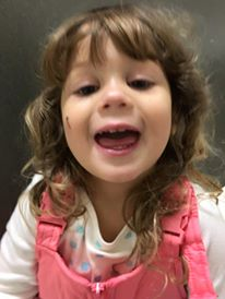 A little girl wearing snowdants smiles while taking a selfie