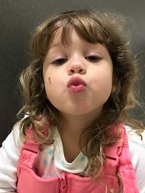 A little girl kisses the world while she takes a selfie.