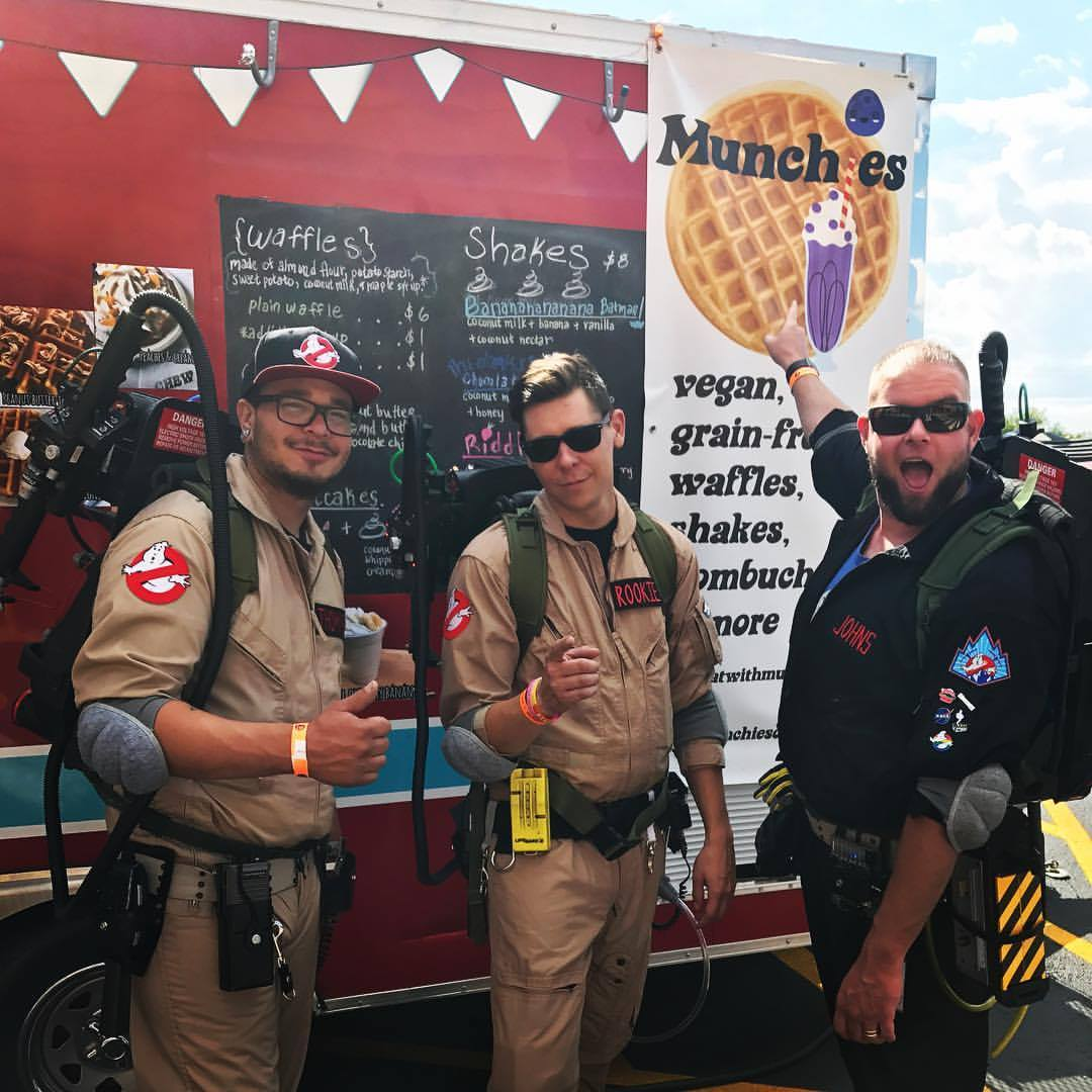 The Ghostbusters stand in front of Munchies food trailer at Comic