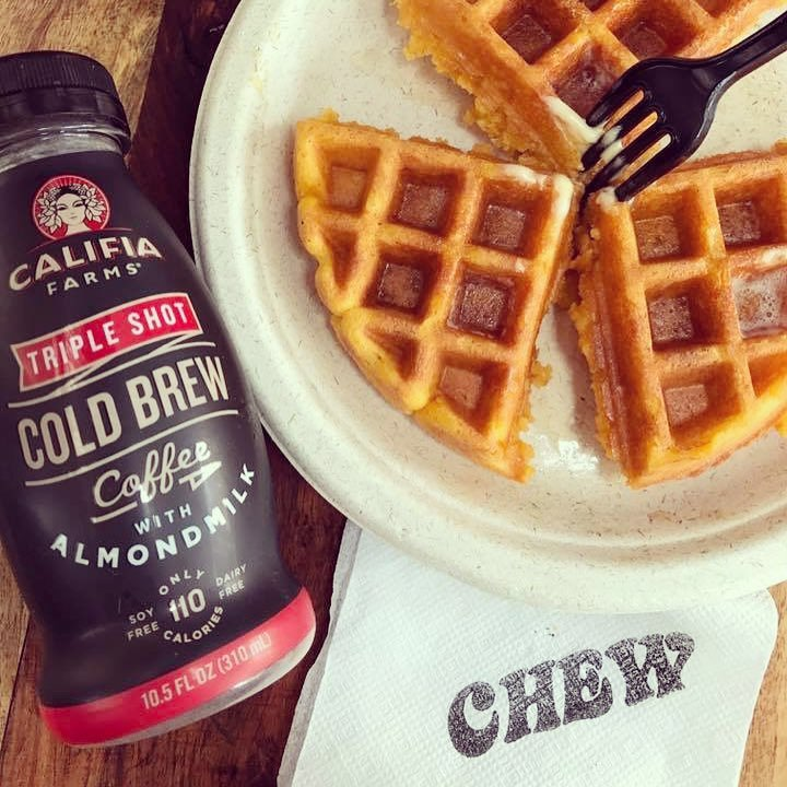 Three pieces of a Belgian waffle next to a Califia farms cold brew coffee and a CHEW napkin.