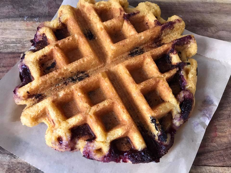 A jam-packed Belgian waffle on a wooden cutting board.