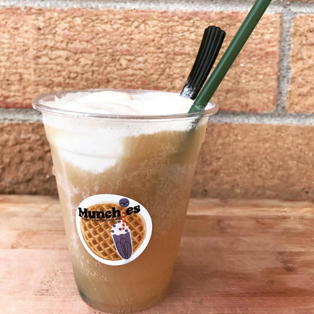 a root beer float made of wild root kombucha and coconut ice cream on a wooden cutting board in front of a brick wall.
