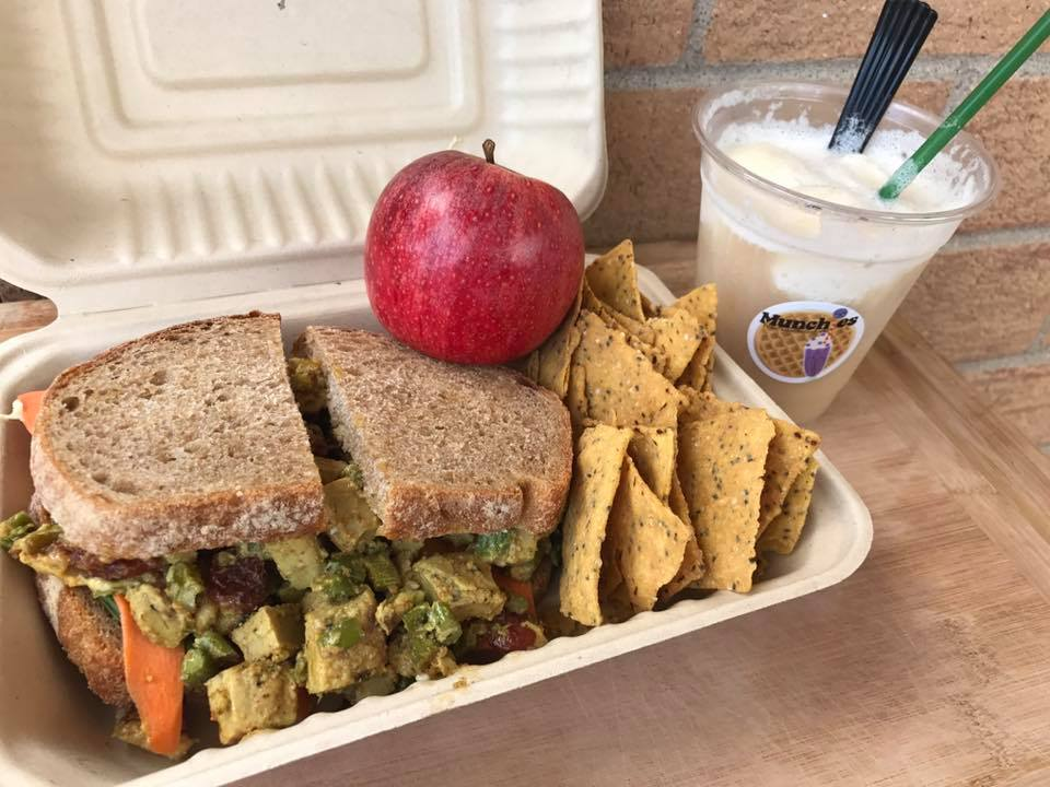Chik'un curry sandwich lunch box with Way Better tortilla chips, an apple, and a wild root bear float made with wild root kombucha and coconut ice cream.