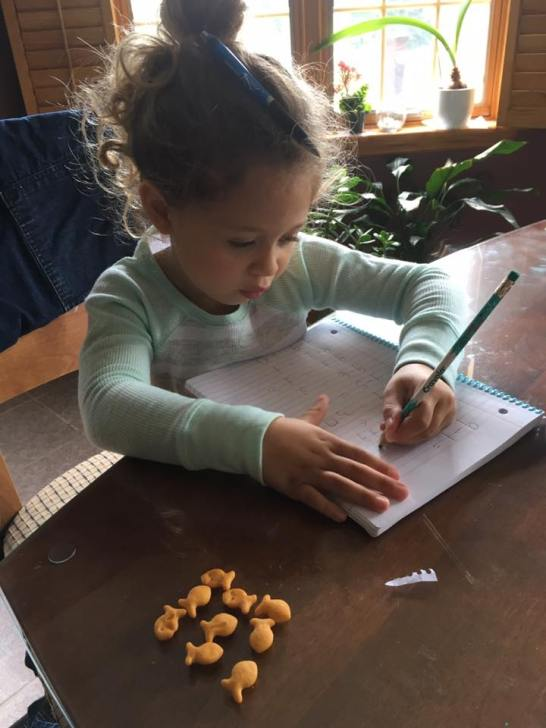 Mia, age 5, learning basic addition on paper for the first time.