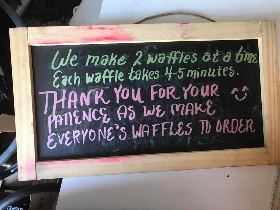 "A chalkboard sign reads ""We make 2 waffles at a time. Each waffle takes 4-5 minutes. Thank you for your patience as we make everyone's waffles to order."""