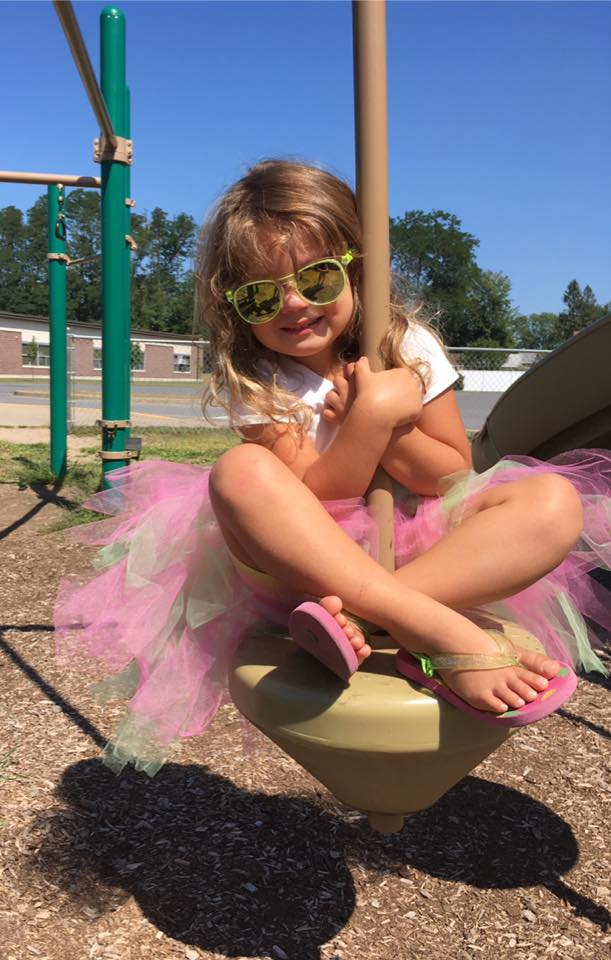 A little girl wearing a tutu, flip flops, and sunglasses plays on a playground.