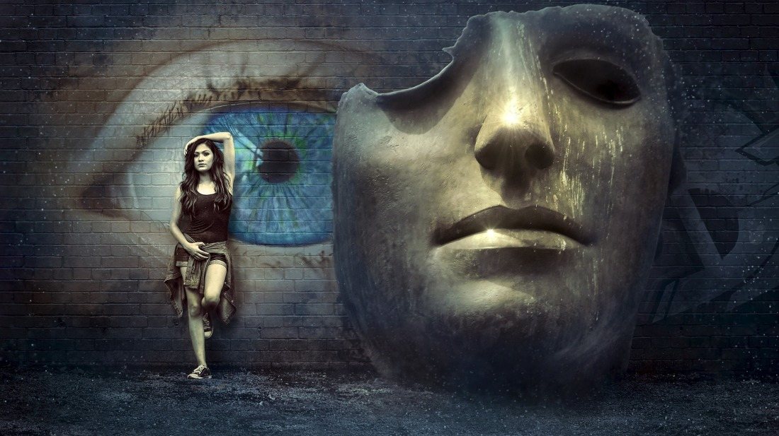 Millennial woman leaning against a wall with a large eye painted on it next to a giant cracked mask