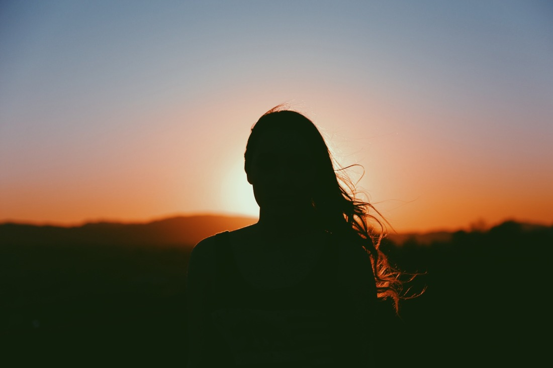 Silhouette of a millennial woman facing the sunset