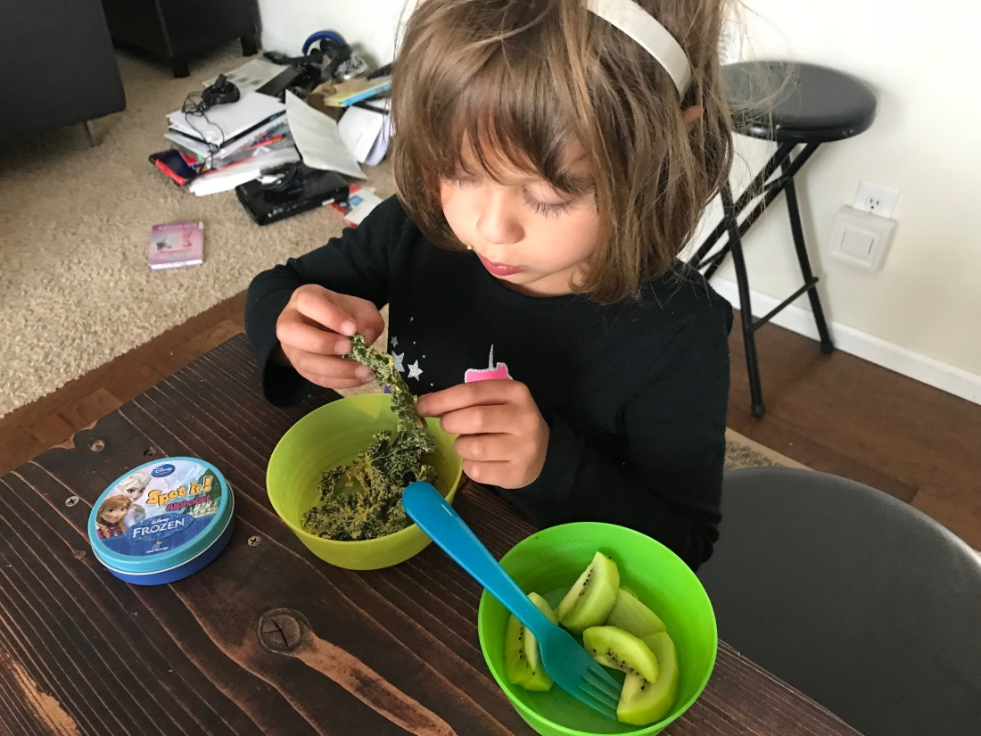 a girl eats cheezy kale chips and kiwi.