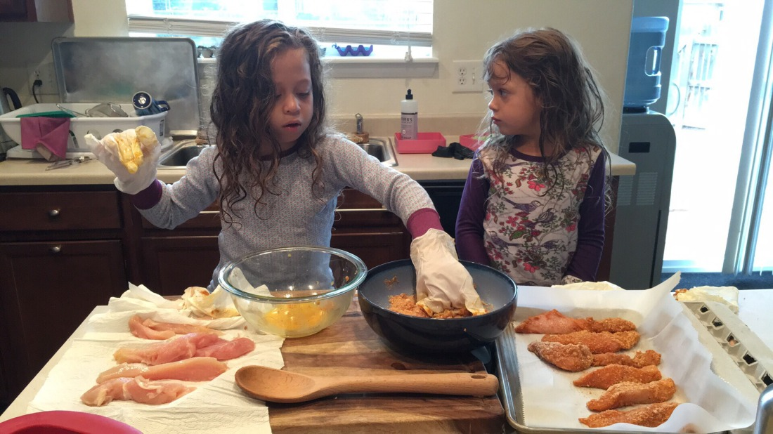 Two girls make homemade chicken tenders in a kitchen.